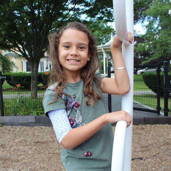 Little girl with a PICCPerfect PICC line cover on her arm smiling on a jungle gym